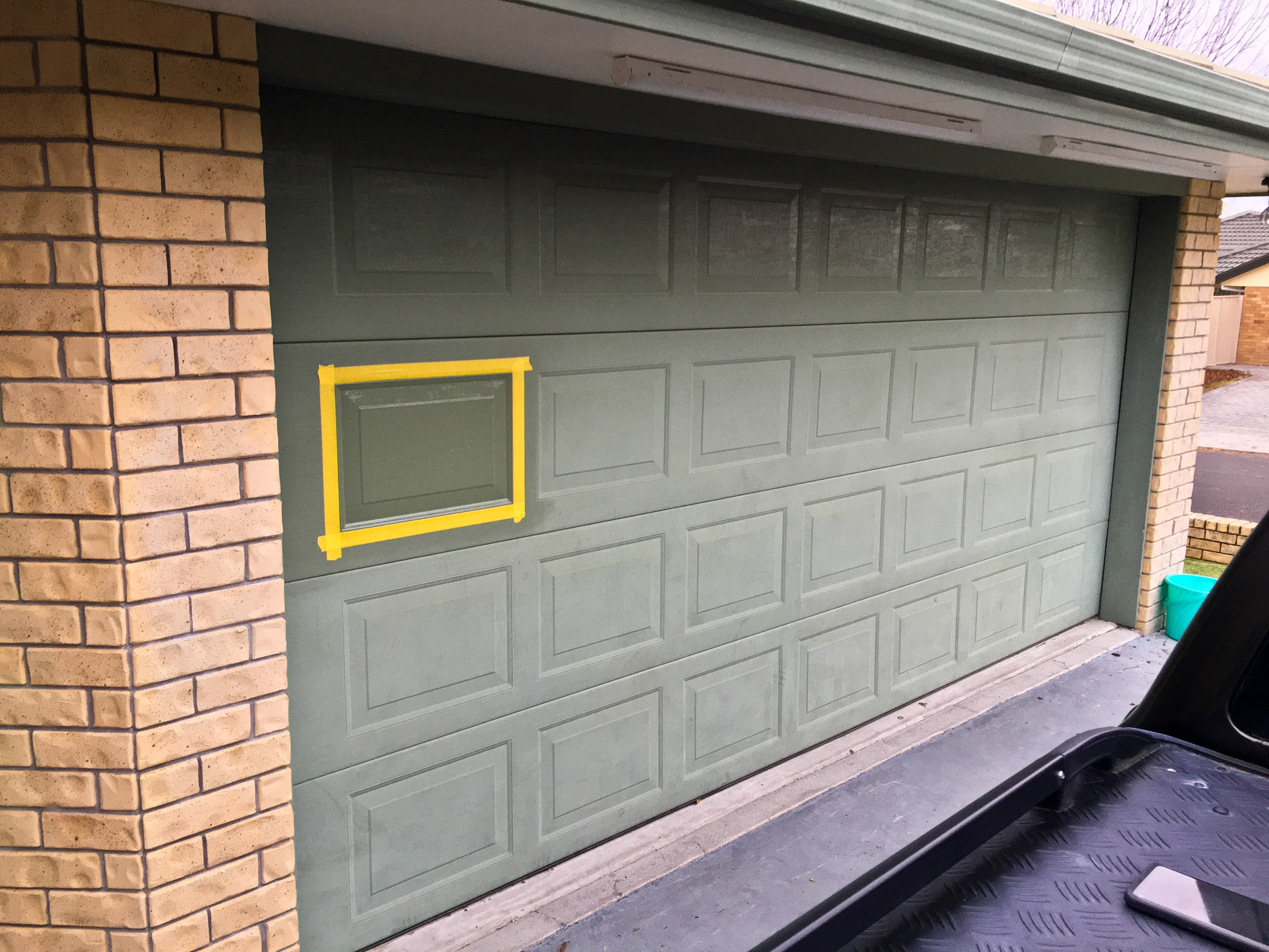 Wider view of garage door section after coating applied
